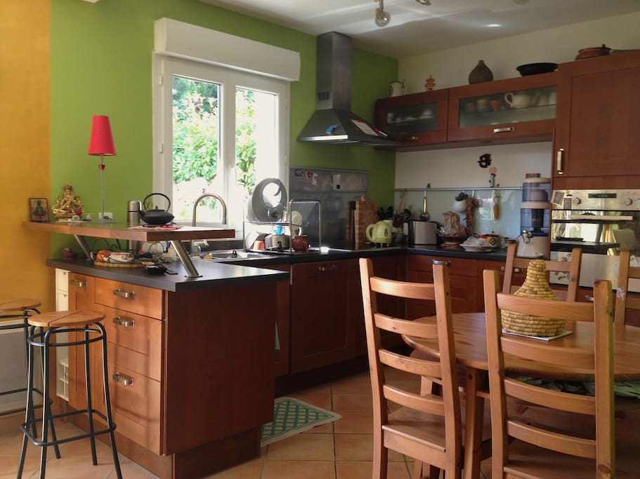 Une cuisine américaine lumineuse, toute équipée, lave vaisselle, four, 4 plaques vitrocéramiques.