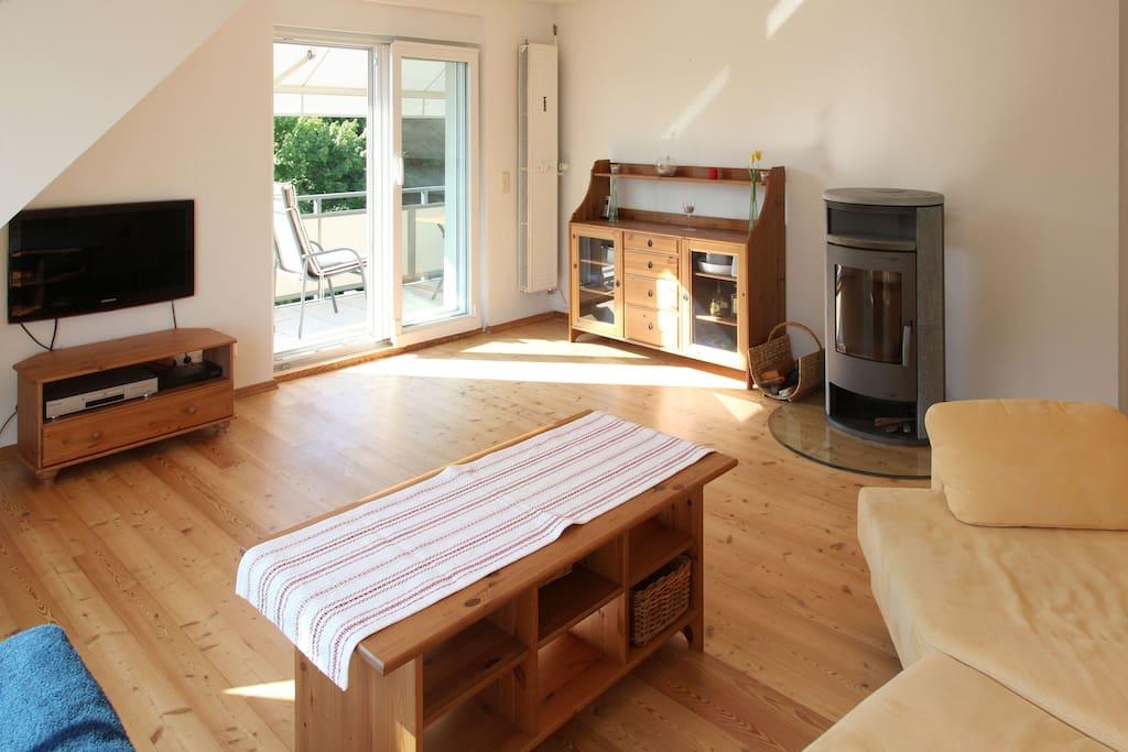 Wohnzimmer mit Zugang zum Balkon und Kaminofen - living room with access to balcony and oven