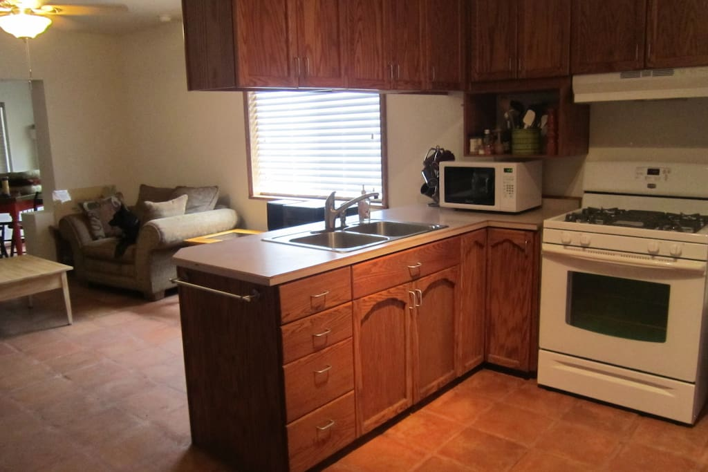 View of kitchen gas stove, looking into living area.