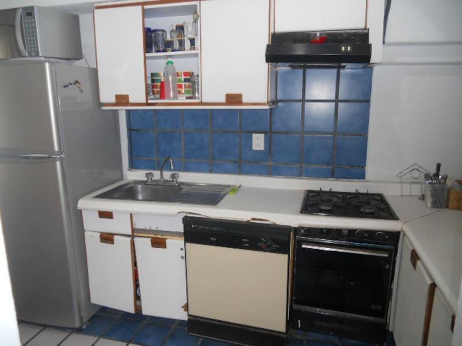 Cocina en el primer piso con refrigerador, estufa, orno de microondas, fregadero y closet (incluye servicio de vajilla y cubiertos).