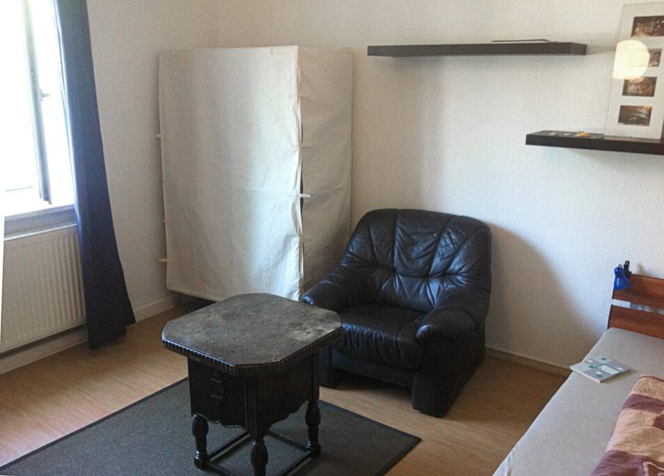 Sehr geräumiges Zimmer mit Sessel, Tisch, Schrank und Fenster zur Straße. Spacious room with possibility to store your things.