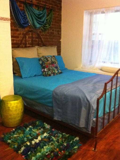 Queen size bed outfitted for a Summer stay.