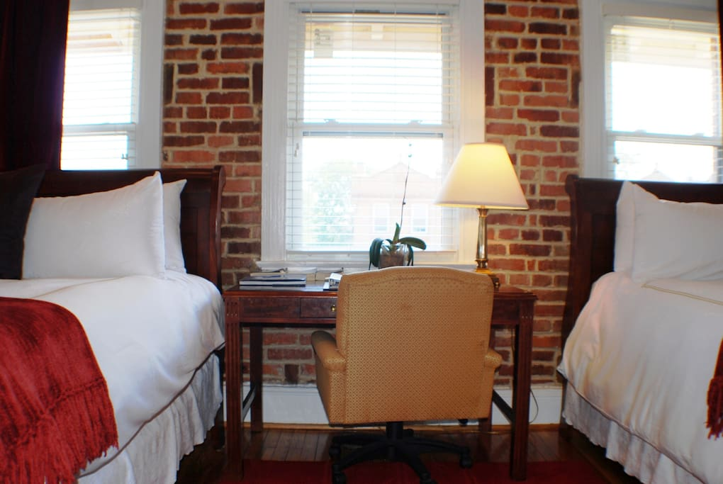 Two queen size comfortable beds, a desk, lamp, chair and two large windows in bedroom.