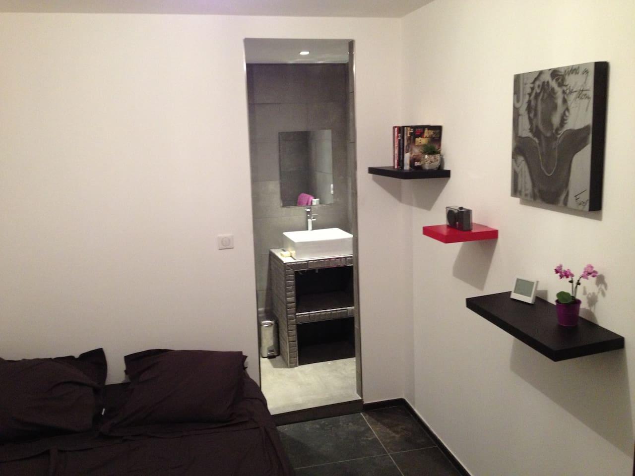 La chambre avec sa petite salle de bain