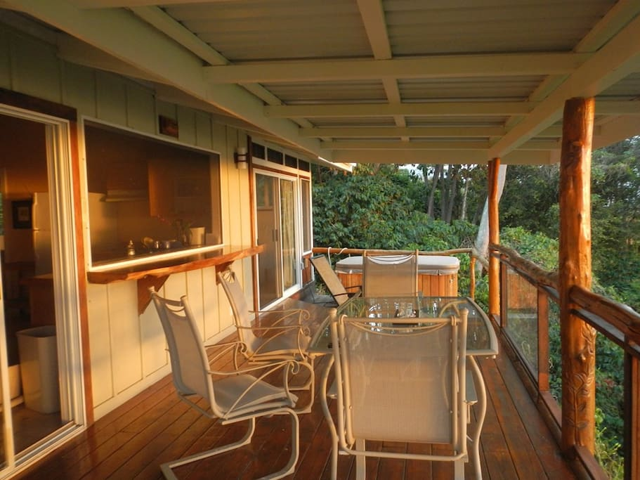 Large covered deck with outdoor dining table and bar.