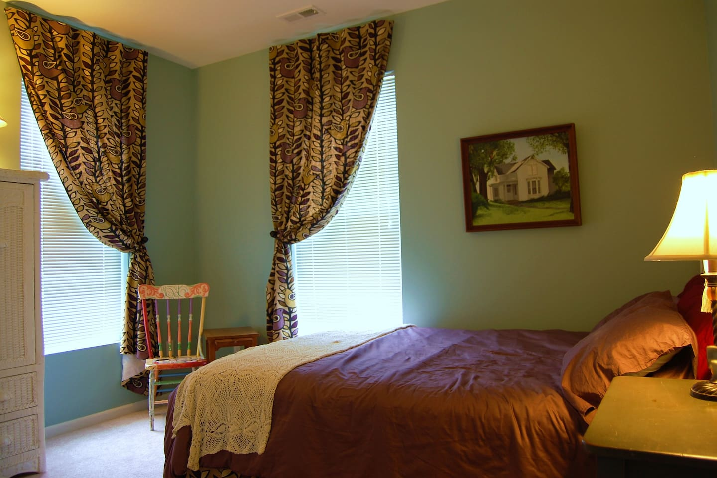 Queen bed, high ceilings, and workable drapes make this a cozy room