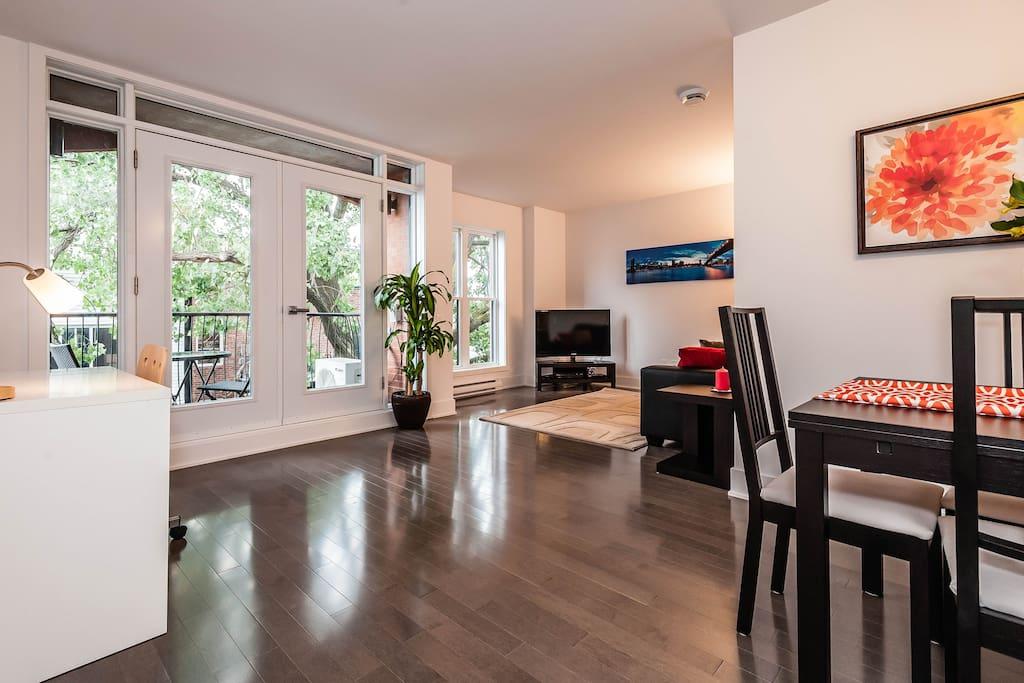 Grande pièce aire ouverte avec salle à manger, bureau et salon.