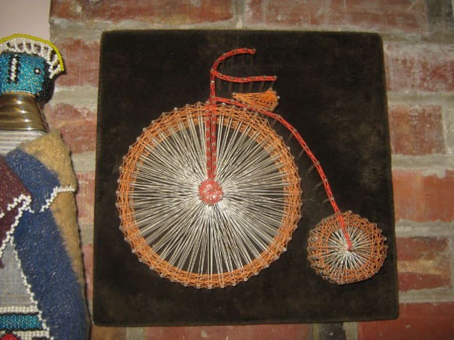"""This awesome bicycle string-art piece is just one of the """"odd but beloved"""" artworks in the Wooly Wabi-Sabi Room."""