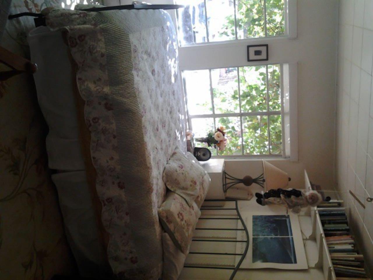 sun-lit room with queen bed, dresser, closet, and garden views