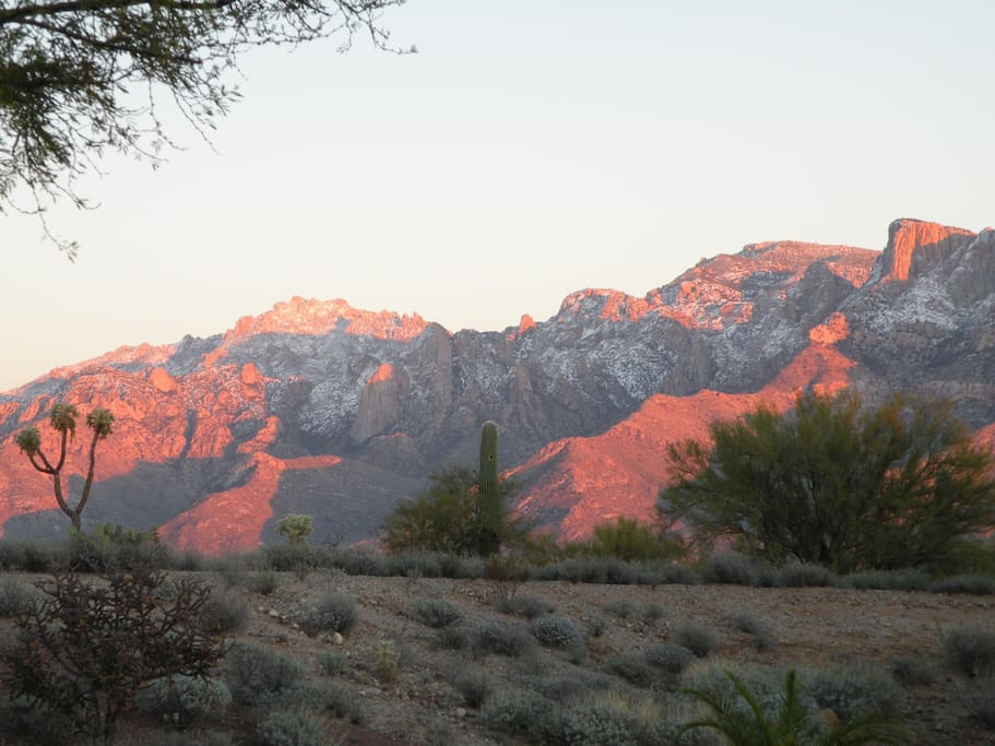 Photo taken in front of house shows sunset glow on the Catalina mountains.
