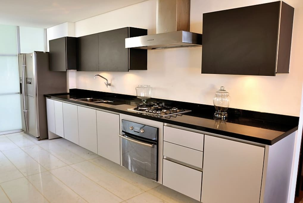 Kitchen, black granite counter, gas oven and stovetop, enclosed microwave, side by side fridge/freezer, service area with washer/dryer behind sliding glass door