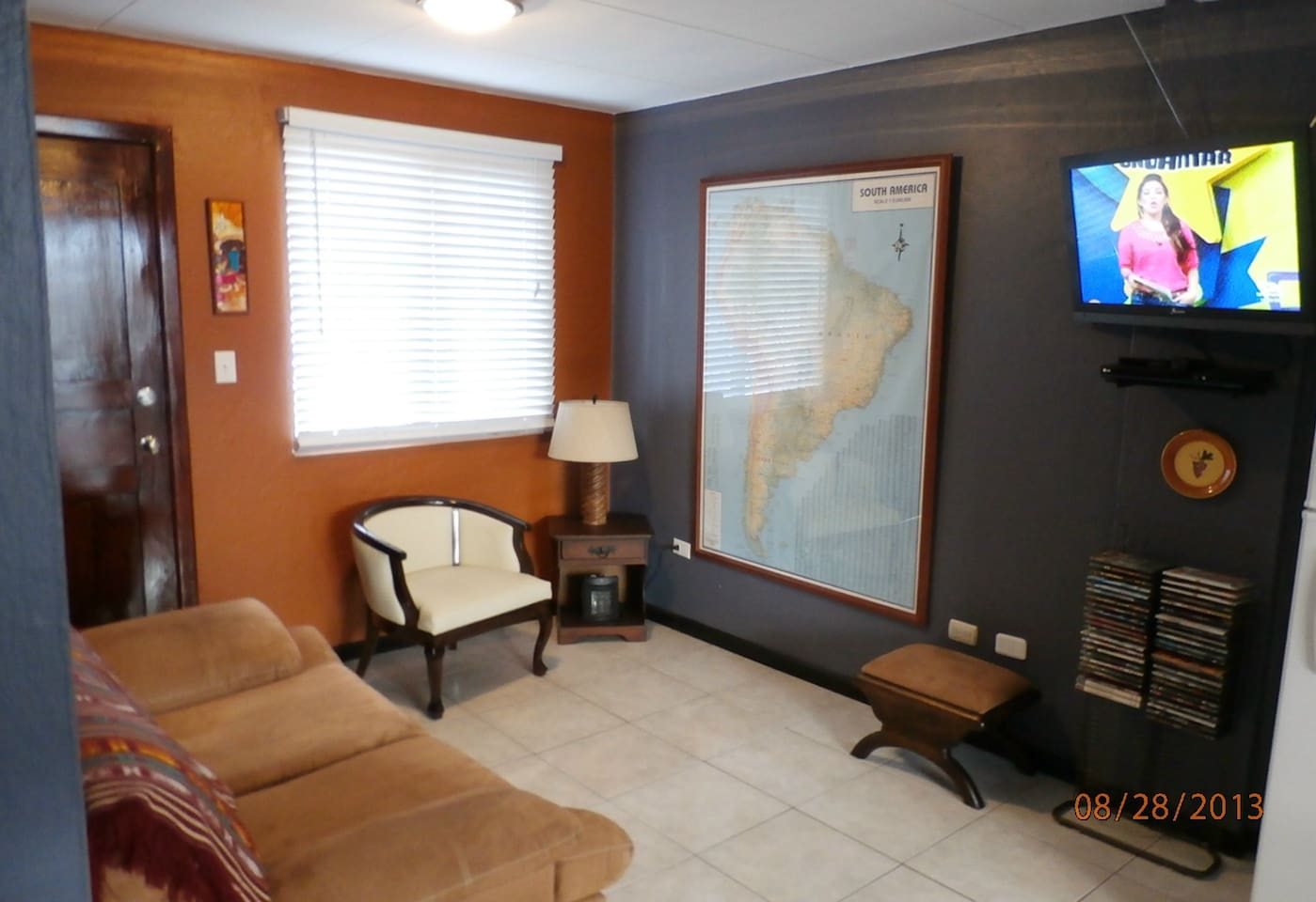 Living area with sofa, chair, flat-screen TV, DVR, stereo, and giant map of South America!