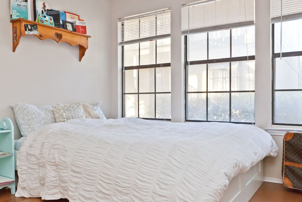A queen-sized bed against some lovely windows.