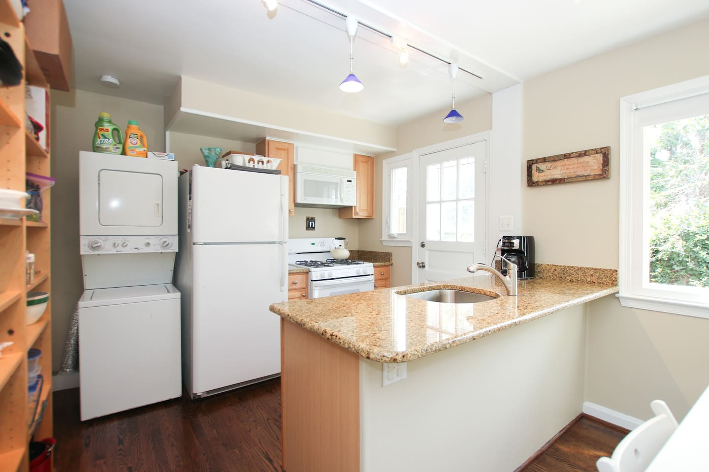 Kitchen with beautiful granite counter, gas stove, dishwasher, full fridge and washer/dryer