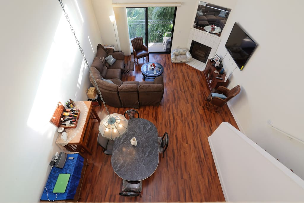 This is the view of the living room, balcony, and dining area from the loft space.
