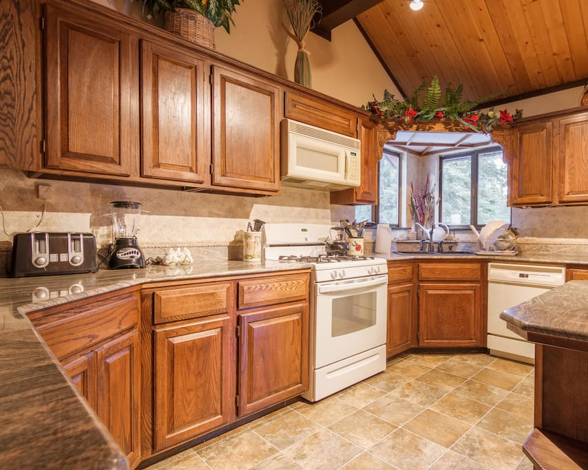 Well provisioned kitchen with island, and breakfast nook+ sliding door to outside deck
