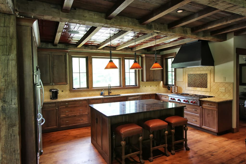 Chefs kitchen with 8 burner Wolf stove, double ovens, and large island for gathering.