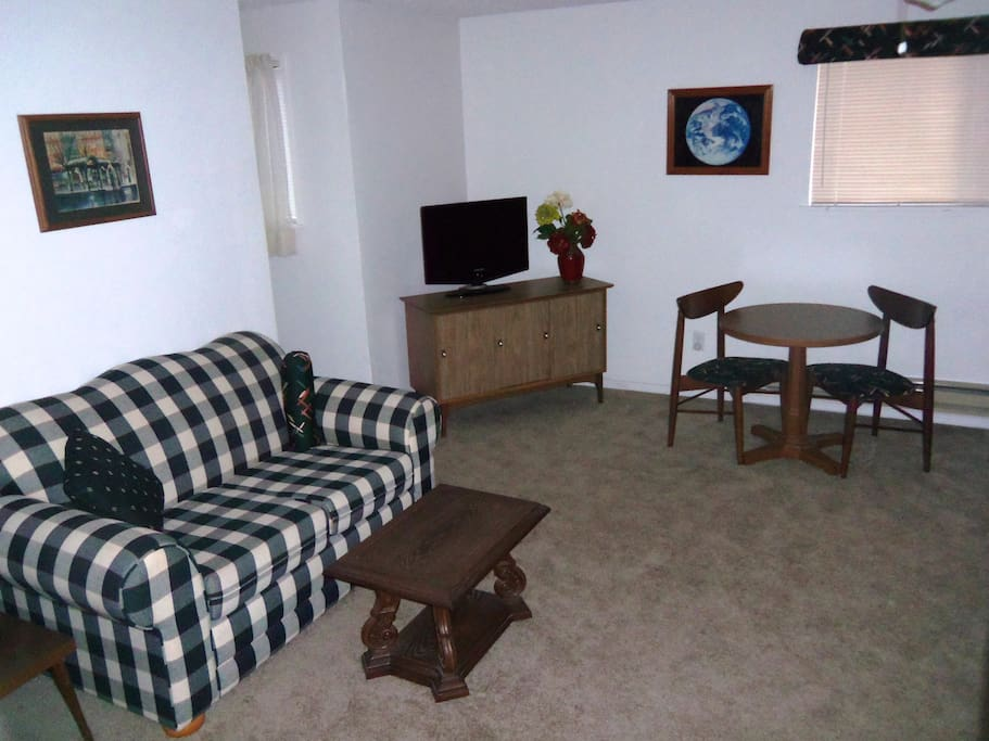 East side of living room includes game table, entertainment center and love seat sofa.