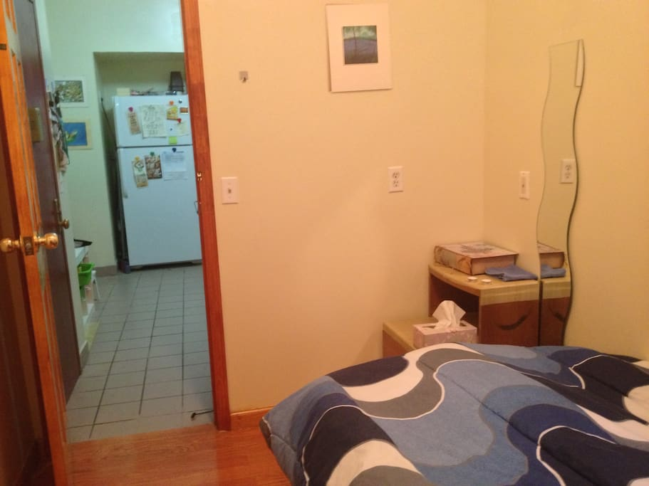 Bedroom with twin bed, air-conditioner and closet. Windows look onto a private alley.