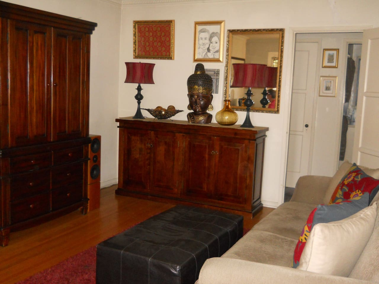 Living room with full size couch and entertainment center.