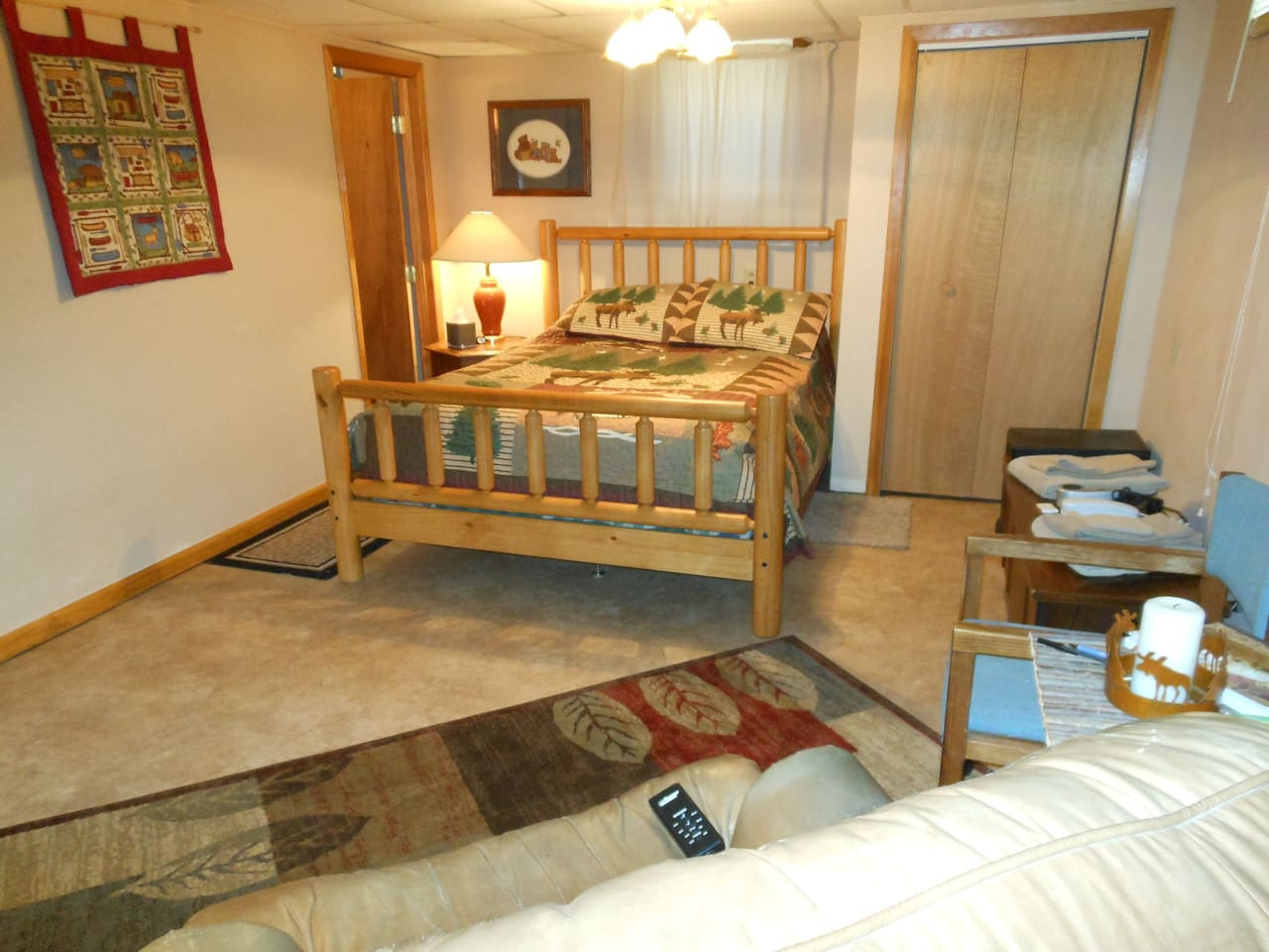 Moose & bear motif, with two windows, bathroom, shower & sauna through door on left. Private & spacious with heat/massage recliner one one side of bedroom also! Cot under bed for 3rd person if needed.