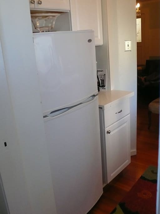 Fully equipped kitchen with refrigerator, gas stove, coffee maker and cooking utensils.