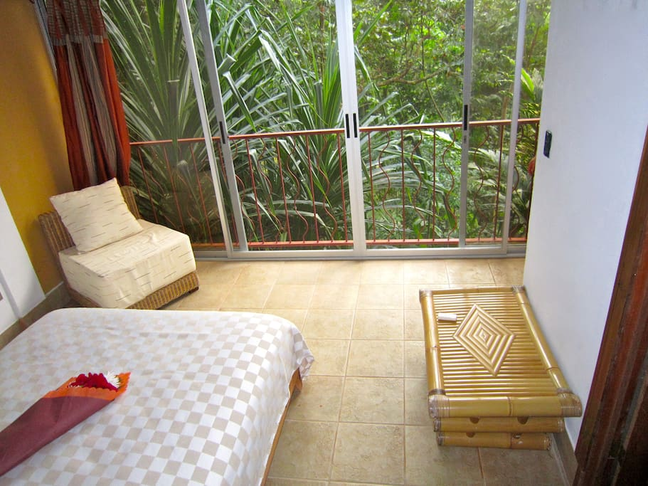 Bedroom with sliding glass doors facing the beautiful jungle.