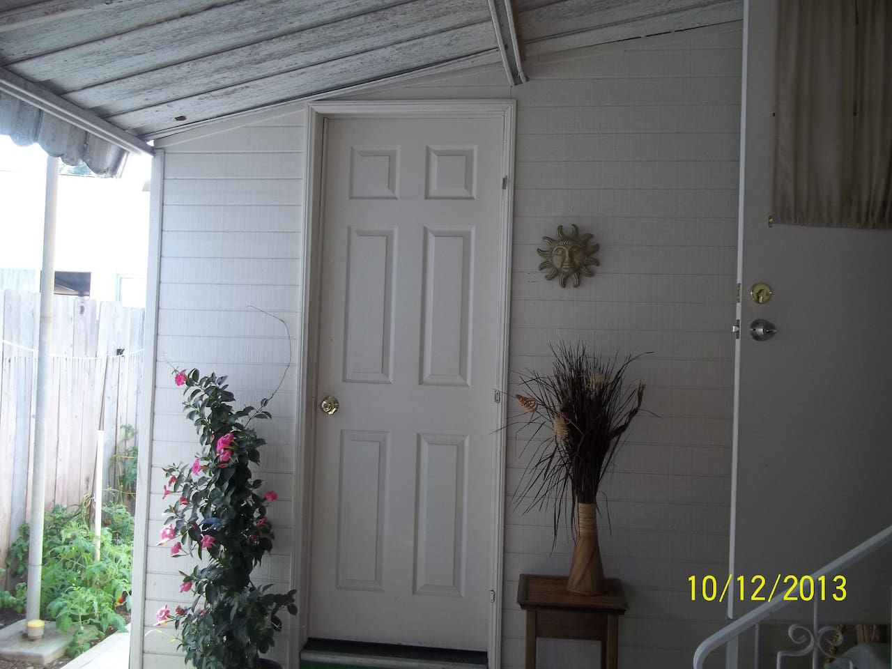 PRIVATE ENTRANCE is the door in the center of the picture.  On the right is the open door to the main house.  On the left side of the picture is a tomato garden and a sidewalk that leads to an enclosed back patio.  Picture is taken from inside the enclose