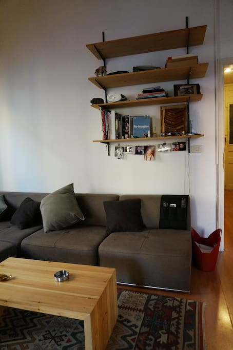 a huge seating space with shelves on top of entrance side