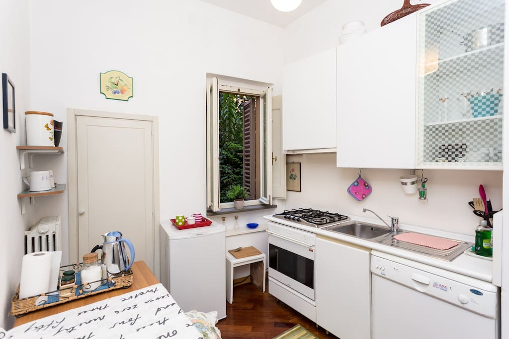 Kitchen with window over looking inside garden, fridge,dishwasher,oven/grill and utencils