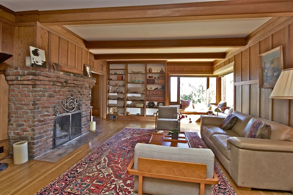 The living room with its clinker brick fireplace, redwood panelling, bookcase and water views.