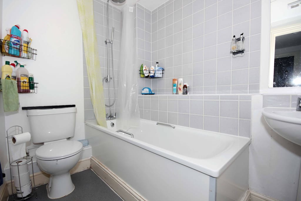 Clean fresh bathroom with a full size bath and convenient shower.