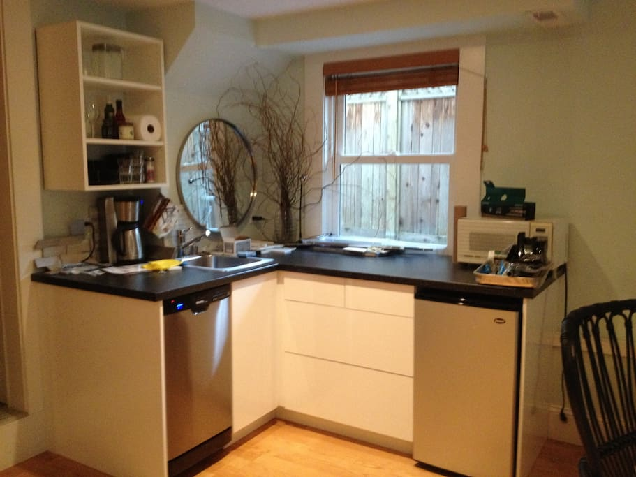 New kitchenette with dishwasher, fridge, induction cooktop, microwave, dishes, glasses, pots and pans.