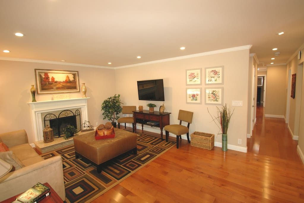 Living room with wood burning fireplace and flat screen TV.