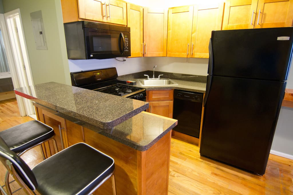 Modern Gas Kitchen with Microwave and Dishwasher.  Equipped with Dishes