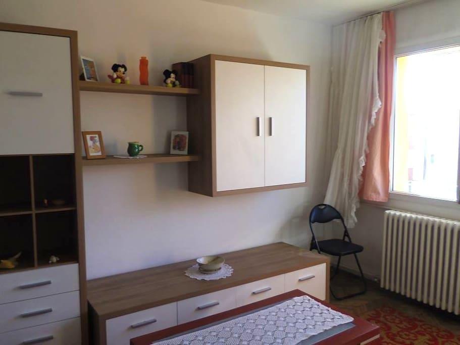 Bedroom with window towards balcony.