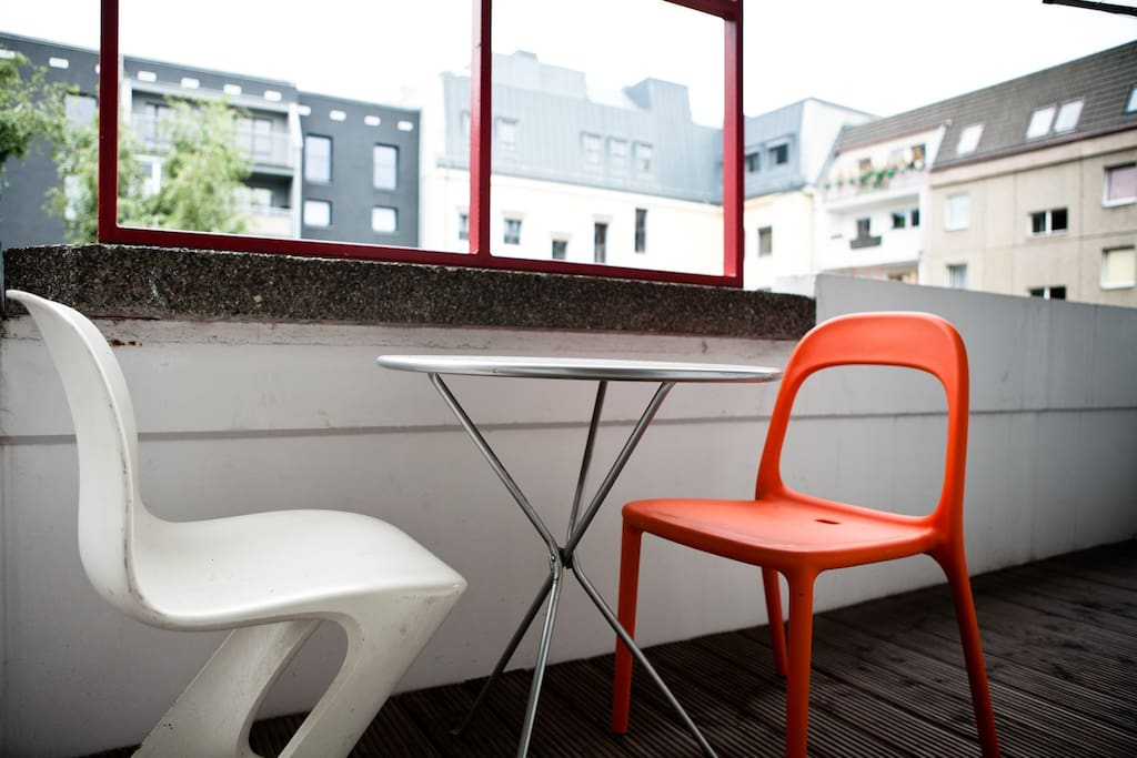 A big balcony to the backyard with a wooden douglasie floor, white chair is german classical 70ies chair from east germany