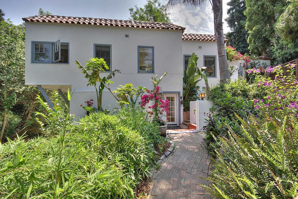 A charming Mediterranean style home set amid lush landscaping.
