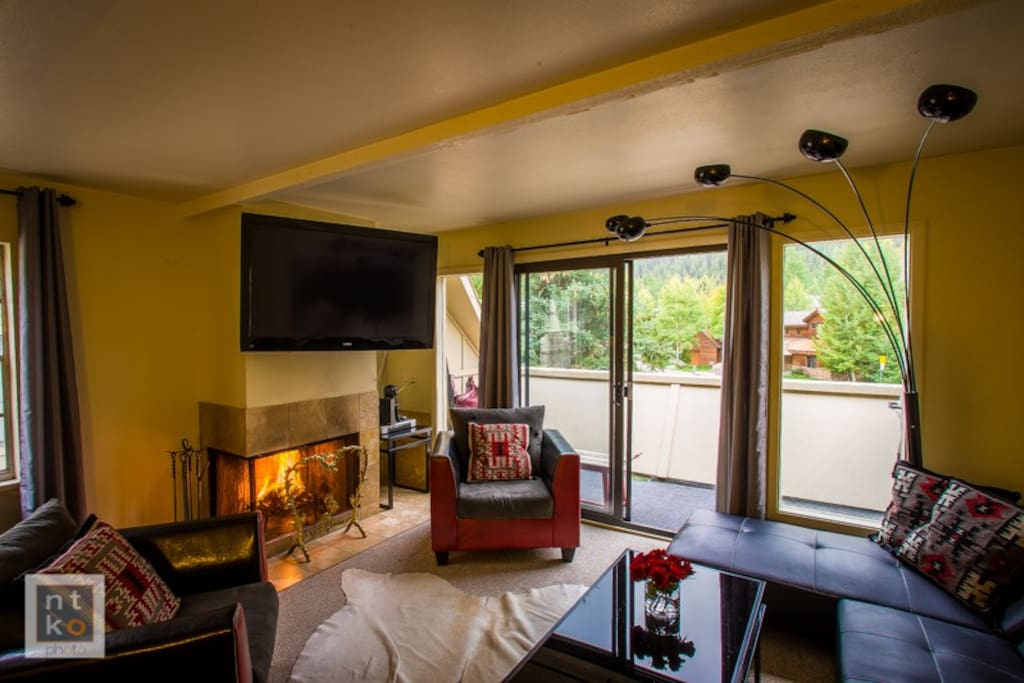 Newly furnished mountain chic style living room with a wood burning fireplace.  Step out on the balcony to enjoy views of Aspen Mountain.