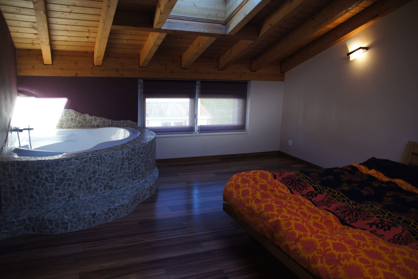 The large bedroom under the roof with bathtub and TV