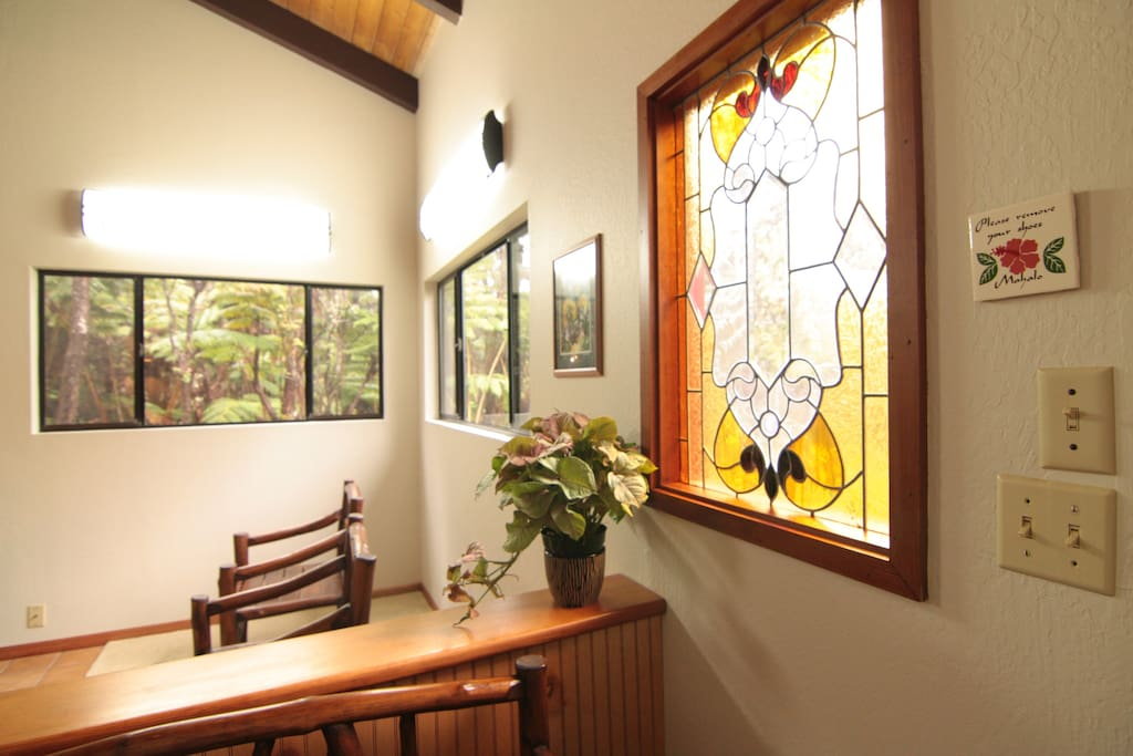 A view of a custom stained glass window  by local artist Beverly Jackson in the living room.