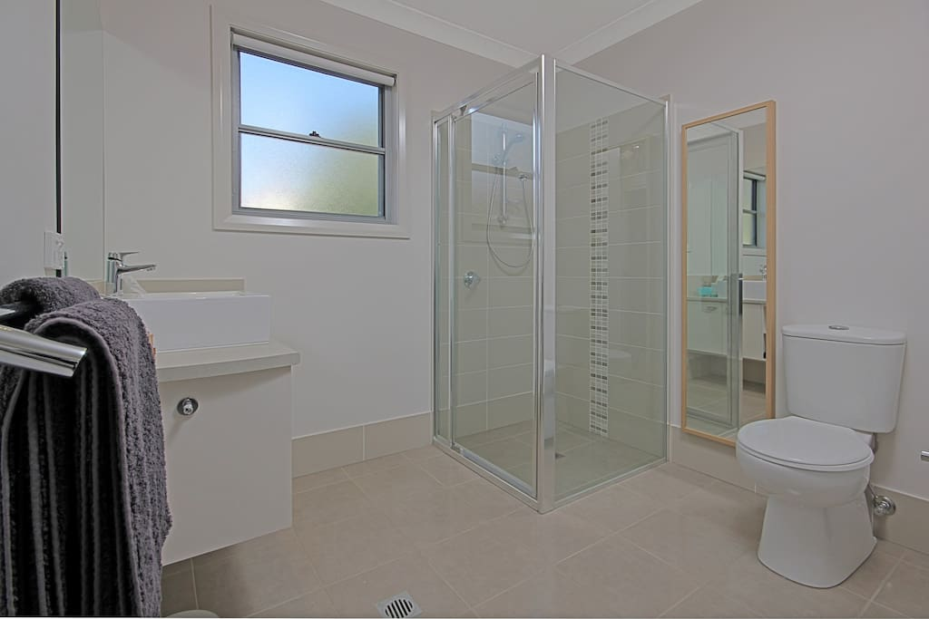 Modern ensuite with hair dryer and personal care products supplied