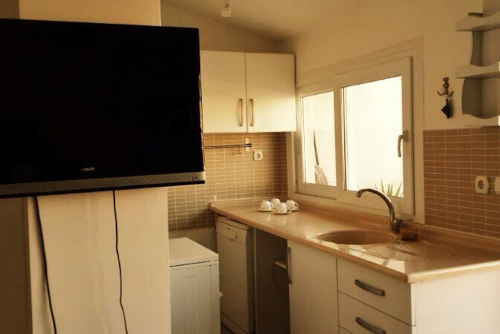 Open fully equipped kitchen with fridge, water boiler, dish washer, flat screen tv with satellite, gas stove...