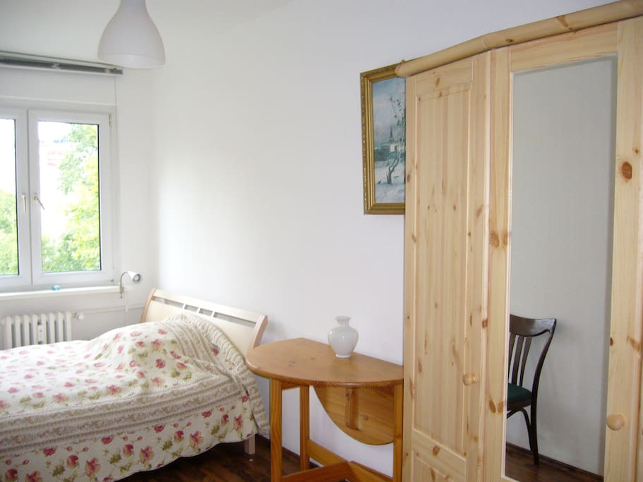 That's how the bedroom looks like now : a new three-door wooden wardrobe and a round wooden table next to the bed