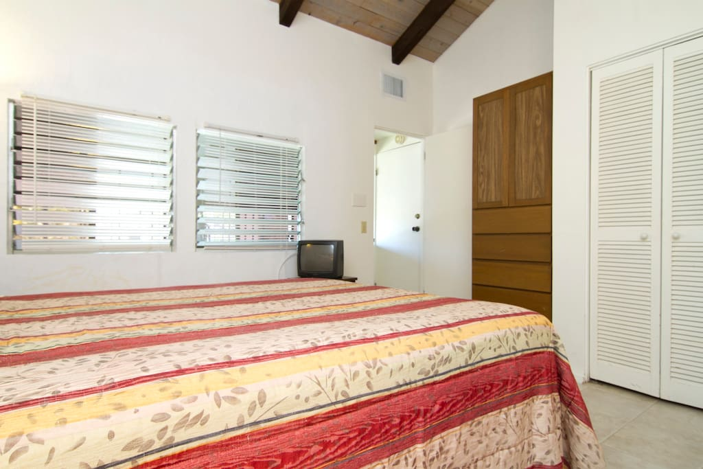 Interior guestroom with queen bed, TV, air conditioner and WiFi.