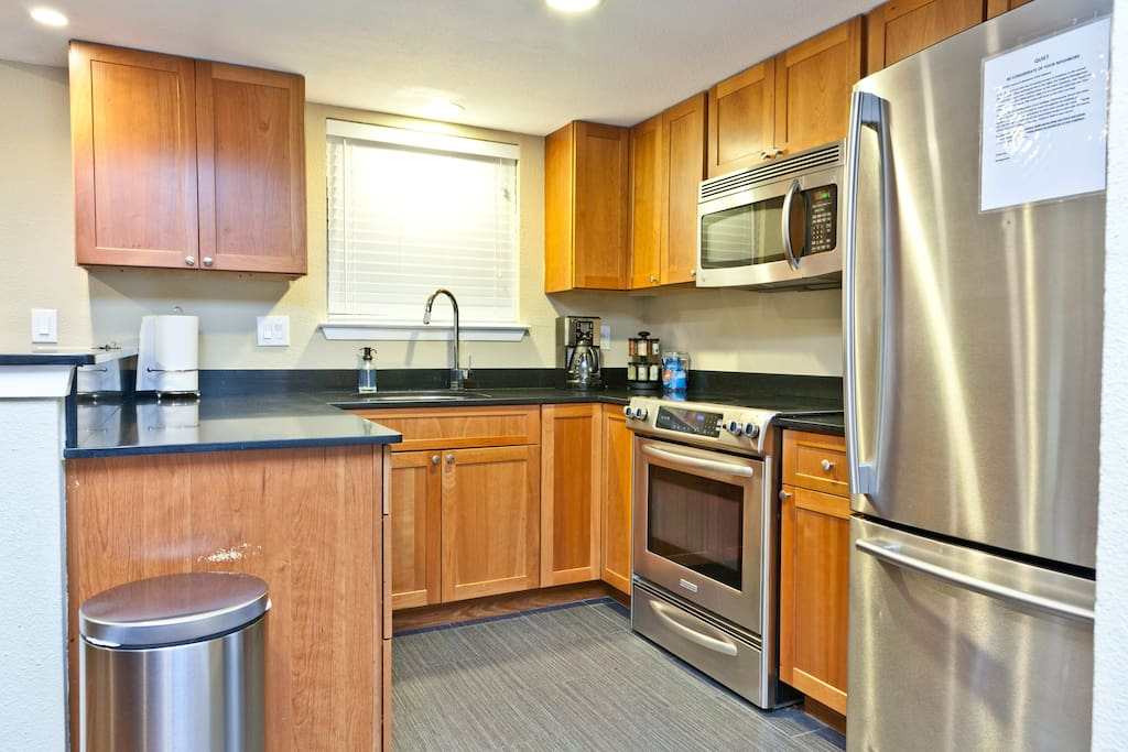 Kitchen with newer cabinets and stainless dishwasher, microwave, stove, and refrigerator with ice-maker.