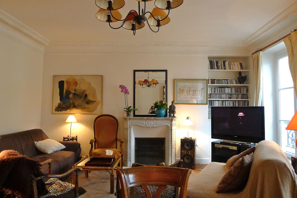 A cosy living room, with a marble fireplace, CDs, flatscreen TV, fine arts
