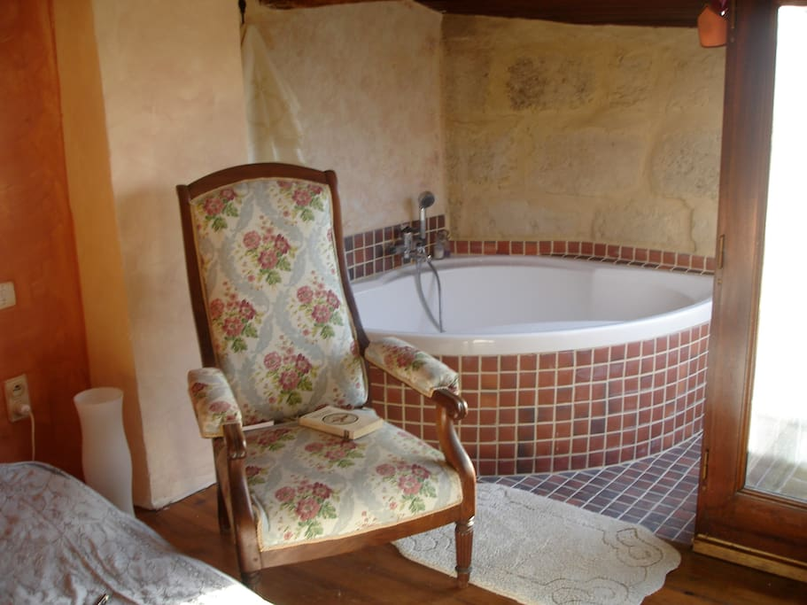 The bedroom, with the corner bathtub and the terrace with the view of the village roofs and the valley. Absolute privacy!
