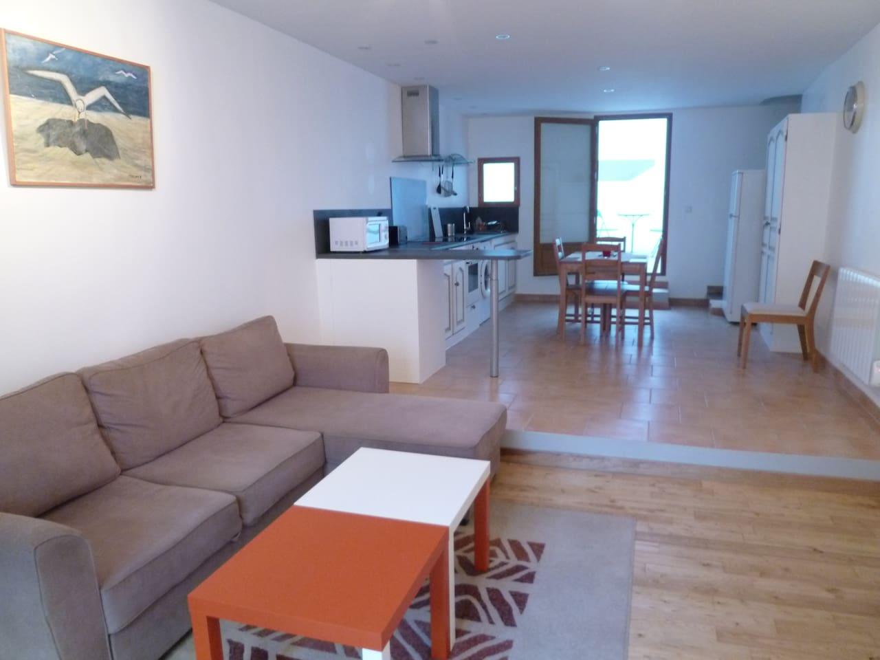 Le séjour, chaleureux et son plancher en châtaigner, forme un grand espace de vie avec la cuisine équipée. Canapé convertible en grand lit 2 places.