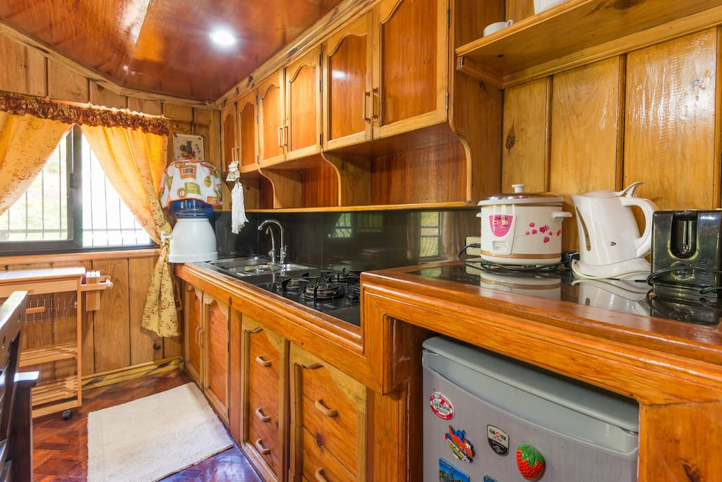 Kitchen with refrigerator, gas stove, pots, pans, cooking utensils, crockery and cutlery.